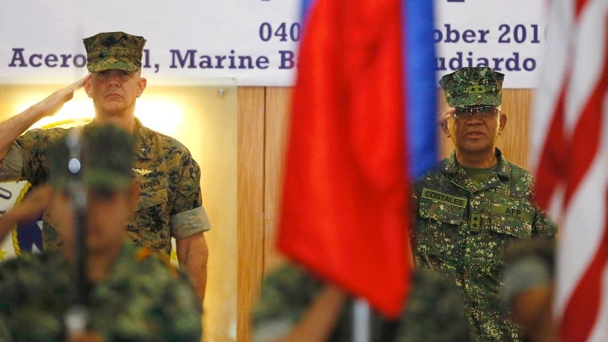 U.S. Marines Brig. Gen. John Jansen of the 3rd Marine Expeditionary Brigade and Maj. Gen. Andre Costales, Commandant of the Philippine Marines Corps, salute the flags at the opening ceremony for the 33rd joint US-Philippines amphibious landing exercises dubbed PHIBLEX at the marines corps in Taguig city east of Manila, Philippines Tuesday Oct.4,2016. President Rodrigo Duterte said he was giving notice to the United States, his country's long-standing ally, that joint exercises between Filipino and American troops this week will be the last such drills. He told the Filipino community in Hanoi, Vietnam's capital, last week that he will maintain the military alliance with the U.S. because of the countries' 1951 defense treaty. But he said this week's exercises will proceed only because he did not want to embarrass his defense secretary.(AP Photo/Bullit Marquez)