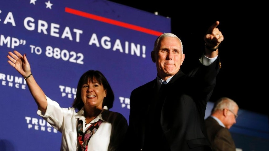 Republican vice presidential nominee Indiana Gov. Mike Pence, arrives with his wife, Karen, at a campaign rally at Cox Transportation Services in Ashland, Va., Monday Oct. 3, 2016. (Shelby Lum/Richmond Times-Dispatch via AP)