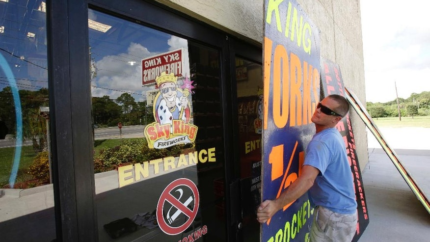 Andrew Esser boards up the glass doors at the entrance of Sky King Fireworks in preparation for Hurricane Matthew, Wednesday, Oct. 5, 2016, in Cocoa, Fla. (AP Photo/John Raoux)