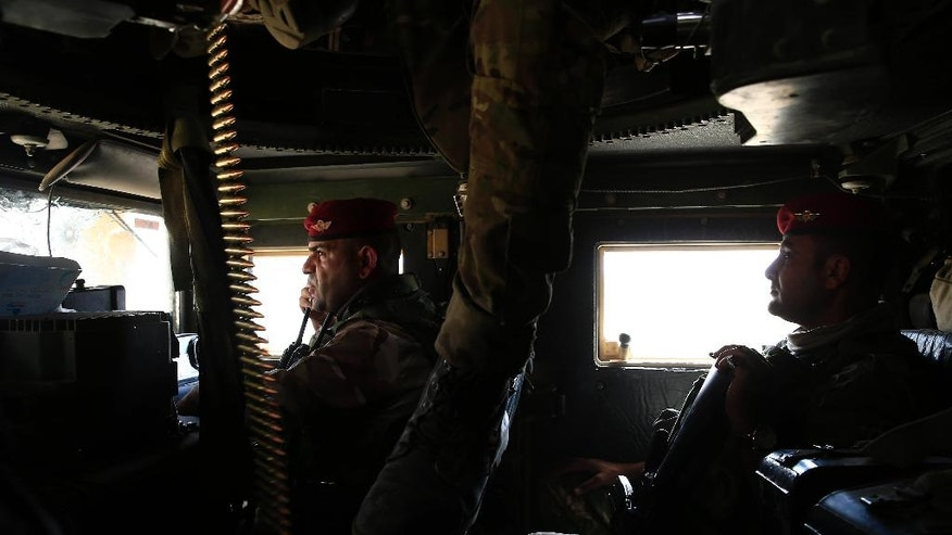 Iraqi soldiers drive towards the frontline in a humvee outside the town of Qayyarah on Tuesday, Oct. 4, 2016. Qayyarah has become an important staging ground for military and humanitarian efforts ahead of the Mosul operation. (AP Photo/Bram Janssen)