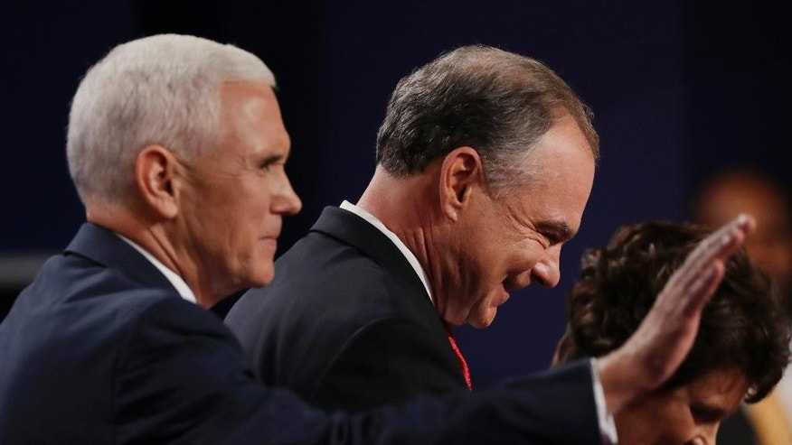 Democratic vice-presidential nominee Sen. Tim Kaine leaves the stage with Republican vice-presidential nominee Gov. Mike Pence during the vice-presidential debate at Longwood University in Farmville, Va., Tuesday, Oct. 4, 2016. Right is Anne Holton, wife of vice-presidential candidate Sen. Tim Kaine. (AP Photo/Patrick Semansky)