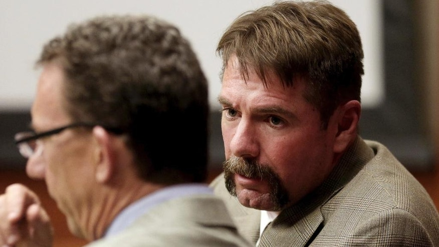 David Watson, right, leans in to speak with attorney Michael Storie during opening statements, Wednesday, Oct. 5, 2016 at Pima County Superior Court in Tucson, Ariz. The trial against a former Arizona fire captain who rose through the ranks as police suspected him in three murders concluded its first day with damming testimony from the defendant's one-time alibi. David Watson is accused of killing his ex-wife, Linda Watson, in August 2000 and then gunning down her mother and her mother's friend three years later. (Mike Christy/Arizona Daily Star via AP)