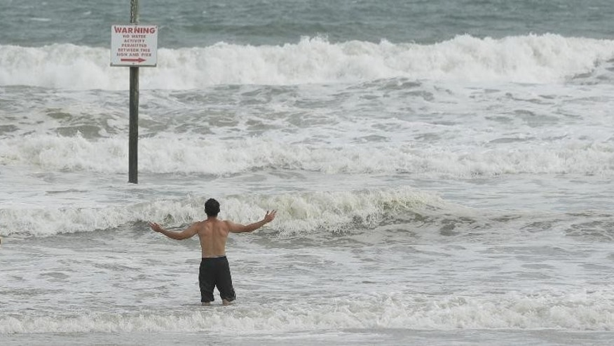 A pair of swimmers take advantage of the high surf from winds associated with Hurricane Matthew Thursday, Oct. 6, 2016, in Daytona Beach, Fla.  Matthew steamed toward Florida with winds of 140 mph Thursday as hundreds of thousands of people across the Southeast boarded up their homes and fled inland to escape the most powerful storm to threaten the Atlantic coast in more than a decade.  (AP Photo/Chris O'Meara)