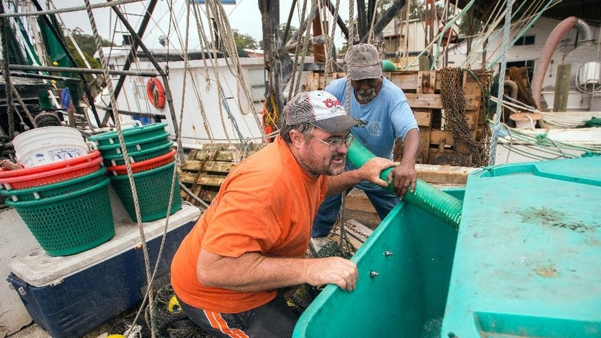 Shrimp boat Captain Wynn Gale, left, and Earnest White, right, fill a ice box with 900 pounds of ice during storm preparations for Hurricane Matthew, Thursday, Oct. 6, 2016, in Darien, Ga. Hurricane Matthew steamed toward Florida with terrifying winds of 140 mph Thursday, and 2 million people across the Southeast were warned to flee inland.   (AP Photo/Stephen B. Morton)