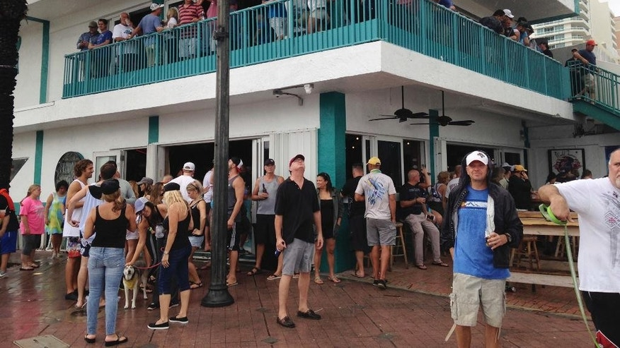 With Hurricane Matthew still far off the coast, people party at the Elbo Room bar in Fort Lauderdale, Fla., on Thursday, Oct. 6, 2016. Dozens of people joined in the festivities and others jogged or swam in the rough surf as Matthew appeared headed well north of the city. (AP Photo/Jay Reeves)