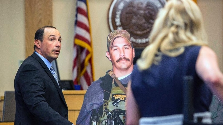 Former Albuquerque police Detective Keith Sandy, stands next to a life-size cut out of himself while assisting the prosecution in demonstrating the distance he maintained during the time of the shooting, Wednesday, Oct. 5, 2016 in Albuquerque, N.M.. Attorneys in the jury trial of two former police officers charged in the killing of a homeless camper have attempted to reconstruct the scene of the standoff that ended with the officers fatally shooting the man in the arms and back.  (AP Photo/Juan Labreche)