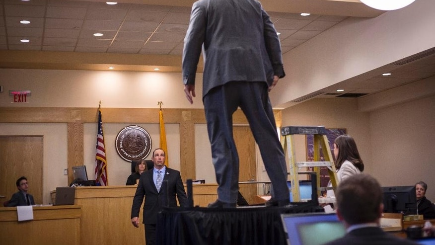 Sam Bregman, representing now retired Dectective Keith Sandy demonstrates the distance at which Sandy stood during the moment James Boyd was shot, Wednesday, Oct. 5, 2016 in Albuquerque, N.M.. Attorneys in the jury trial of two former police officers charged in the killing of a homeless camper have attempted to reconstruct the scene of the standoff that ended with the officers fatally shooting the man in the arms and back.  (AP Photo/Juan Labreche)
