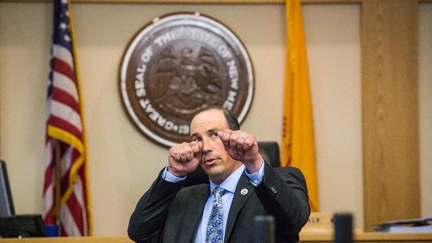Keith Sandy demonstrates the distance at which he stood during the moment James Boyd was shot, Wednesday, Oct. 5, 2016 in Albuquerque, N.M.. Attorneys in the jury trial of two former police officers charged in the killing of a homeless camper have attempted to reconstruct the scene of the standoff that ended with the officers fatally shooting the man in the arms and back.  (AP Photo/Juan Labreche)