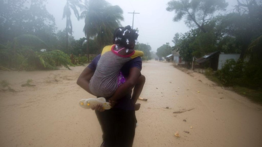 A woman carries a child through a waterlogged street as they head to a shelter under the pouring rain triggered by Hurricane Matthew in Leogane, Haiti, Tuesday, Oct. 4, 2016. Matthew slammed into Haiti's southwestern tip with howling, 145 mph winds tearing off roofs in the poor and largely rural area, uprooting trees and leaving rivers bloated and choked with debris. (AP Photo/Dieu Nalio Chery)