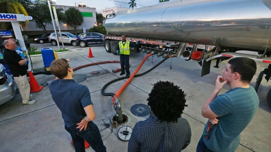 Motorists look on as Wayne Demps with CWC Transportation, center rear, fills the empty tanks of a Marathon gasoline station, Wednesday, Oct. 5, 2016, in Hollywood, Fla. Hurricane Matthew marched toward Florida, Georgia and the Carolinas and nearly 2 million people along the coast were urged to evacuate their homes Wednesday, a mass exodus ahead of a major storm packing power the U.S. hasn't seen in more than a decade. (AP Photo/Wilfredo Lee)
