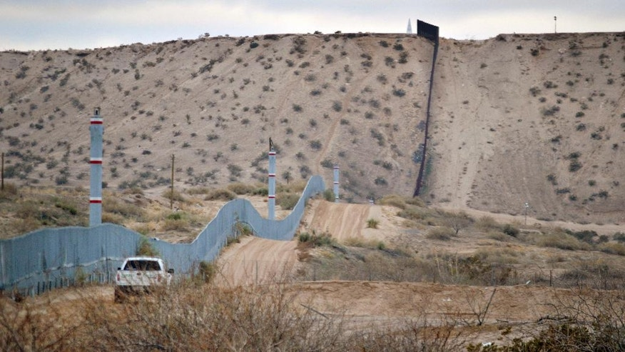 FILE - In this Jan. 4, 2016 file photo, a U.S. Border Patrol agent drives near the U.S.-Mexico border fence in Sunland Park, N.M. U.S. immigration authorities caught barely half the people who illegally entered the country from Mexico last year, according to an internal Department of Homeland Security report that offers one of the most detailed assessments of U.S. border security ever compiled. The report found far fewer people are attempting to get into the U.S. than a decade ago and that 54 percent of those who tried were caught in the year ending Sept. 30, 2015. (AP Photo/Russell Contreras, File)