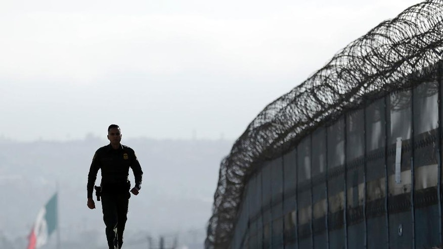 FILE - In this June 22, 2016, file photo, Border Patrol agent Eduardo Olmos walks near the secondary fence separating Tijuana, Mexico, background, and San Diego in San Diego. U.S. immigration authorities caught barely half the people who illegally entered the country from Mexico last year, according to an internal Department of Homeland Security report that offers one of the most detailed assessments of U.S. border security ever compiled. The report found far fewer people are attempting to get into the U.S. than a decade ago and that 54 percent of those who tried were caught in the year ending Sept. 30, 2015. (AP Photo/Gregory Bull, File)