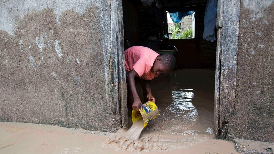 A boy removes mud  and water from his house after Hurricane Matthew flooded it in Les Cayes, Haiti, Thursday, Oct. 6, 2016. Two days after the storm rampaged across the country's remote southwestern peninsula, authorities and aid workers still lack a clear picture of what they fear is the country's biggest disaster in years. (AP Photo/Dieu Nalio Chery)