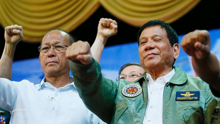 "FILE - In this Sept. 13, 2016 file photo, Philippine President Rodrigo Duterte, center, poses with a fist bump with Defense Chief Delfin Lorenzana, left, during his ""Talk with the Airmen"" on the anniversary of the 250th Presidential Airlift Wing, at the Philippine Air Force headquarters in suburban Pasay city, southeast of Manila, Philippines.  The Philippine defense chief said Friday, Oct. 7, 2016,  that he told the U.S. military that plans for joint patrols and naval exercises in the disputed South China Sea have been put on hold, the first concrete break in defense cooperation after months of increasingly strident comments by the country's new president. Defense Secretary Lorenzana also said that 107 U.S. troops involved in operating surveillance drones against Muslim militants would be asked to leave the southern part of the country once the Philippines acquires those intelligence-gathering capabilities in the near future.  (AP Photo/Bullit Marquez, File)"