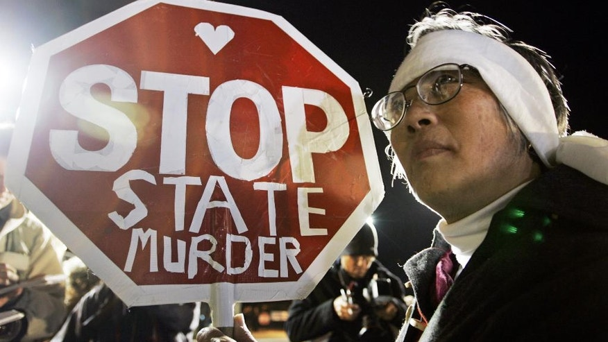"FILE - In this Dec. 12, 2005, file photo, Barbara Chan protests the execution of Stanley ""Tookie"" Williams, the founder of the Crips gang, outside of San Quentin State Prison in San Quentin, Calif. Williams was executed early Dec. 13. California voters face opposite choices to fix the state's broken death penalty. They can repeal capital punishment in November or reform it so convicted murderers are actually executed. (AP Photo/Eric Risberg, File)"