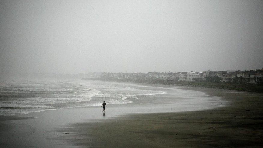 Robert Nicotra braves the wind and rain along the beach on the Isle of Palms, S.C.,  as Hurricane Matthew approaches, Friday, Oct. 7, 2016. (AP Photo/Mic Smith)