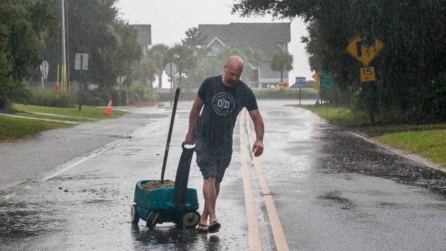 Mike Pendergrast moves a wagon down 41st Ave. full of sand to fill with sand bags around his home on the Isle of Palms as Hurricane Matthew approaches the Isle of Palms, S.C., Friday, Oct. 7, 2016. (AP Photo/Mic Smith)