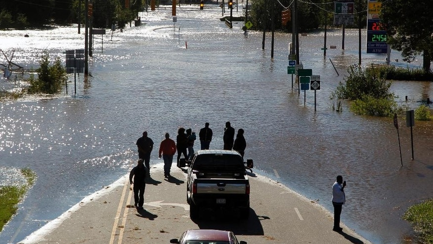 People stop to look and take photos of the floodwaters washing over highway 58 in Nashville N.C., seen from the highway 64 overpass, on Sunday, Oct. 9, 2016. Hurricane Matthew's torrential rains triggered severe flooding in North Carolina on Sunday as the deteriorating storm made its exit to the sea, and thousands of people had to be rescued from their homes and cars.  (Chris Seward/The Charlotte Observer via AP)