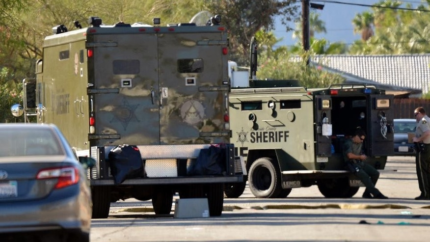 Riverside County Sheriff's Deputies wait in front of a house where a suspect was apprehended about Sunday, Oct. 9, 2016,  in Palm Springs, Calif., the day after multiple Palm Springs police officers were shot after a family disturbance Saturday. (AP Photo/Rodrigo Peña)