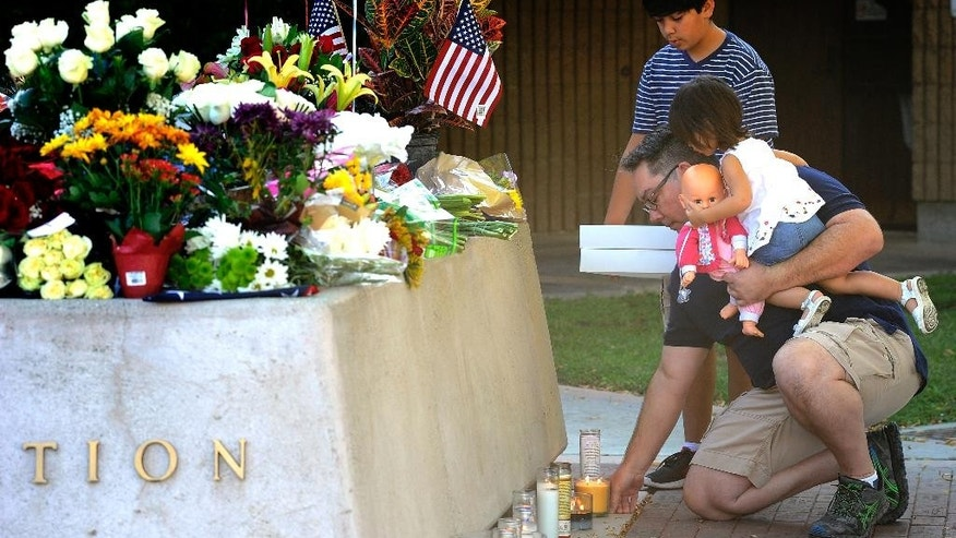 Ron Ristaino, 47, of Rancho Mirage, sets candles at a shrine, while holding his daughter Malayna, 2, and his son Dominic, 12, holds a gift for the peace officers at the Palm Springs police station in Palm Springs, Calif., Sunday, Oct. 9, 2016, the day after multiple Palm Springs police officers were shot after a family disturbance Saturday. (AP Photo/Rodrigo Peña)