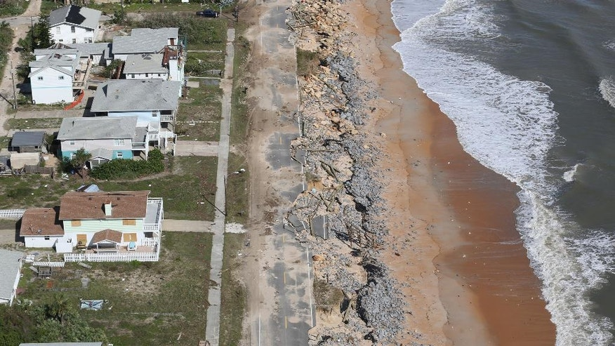Debris lies on a portion of the damaged A1A Highway which was closed in Flagler Beach, Fla., on Saturday, Oct. 8, 2016, after pounding surf from Hurricane Matthew which brushed Florida's east coast. (Red Huber/Orlando Sentinel via AP)