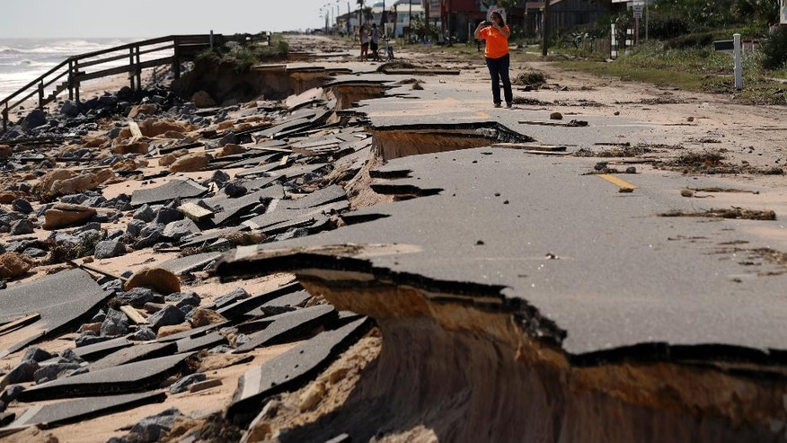 Onlookers walk along a section of highway A1A that was washed out by Hurricane Matthew, Saturday, Oct. 8, 2016, in Flagler Beach, Fla.  The damage from Matthew caused  beach erosion,  washed out some roads and knocked out power for more than 1 million customers in several coastal counties.  (AP Photo/Eric Gay)