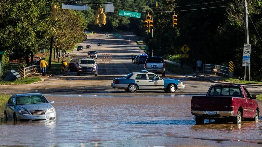 Abandoned cars sit in flood waters on Atlantic Avenue near Crabtree Creek in Raleigh, N.C., after Hurricane Matthew caused downed trees and flooding Sunday, Oct. 9, 2016. Hurricane Matthew's torrential rains triggered severe flooding in North Carolina on Sunday as the deteriorating storm made its exit to the sea, and thousands of people had to be rescued from their homes and cars. (Travis Long/The News & Observer via AP)