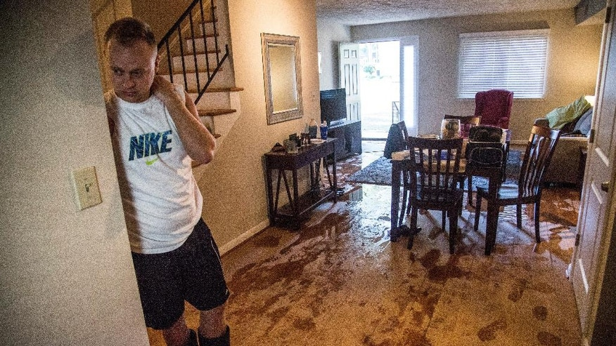 Jeremy Spearman checks on flood damage to his Parkside Five Points Townhomes apartment in Raleigh, N.C., after Hurricane Matthew caused downed trees and flooding Sunday, Oct. 9, 2016. Hurricane Matthew's torrential rains triggered severe flooding in North Carolina on Sunday as the deteriorating storm made its exit to the sea, and thousands of people had to be rescued from their homes and cars. (Travis Long/The News & Observer via AP)
