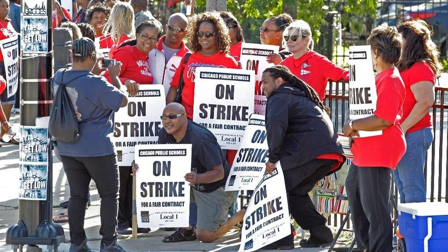 In this September 2012 file photo, Chicago teachers take a group picture as they walk a picket line outside a school.