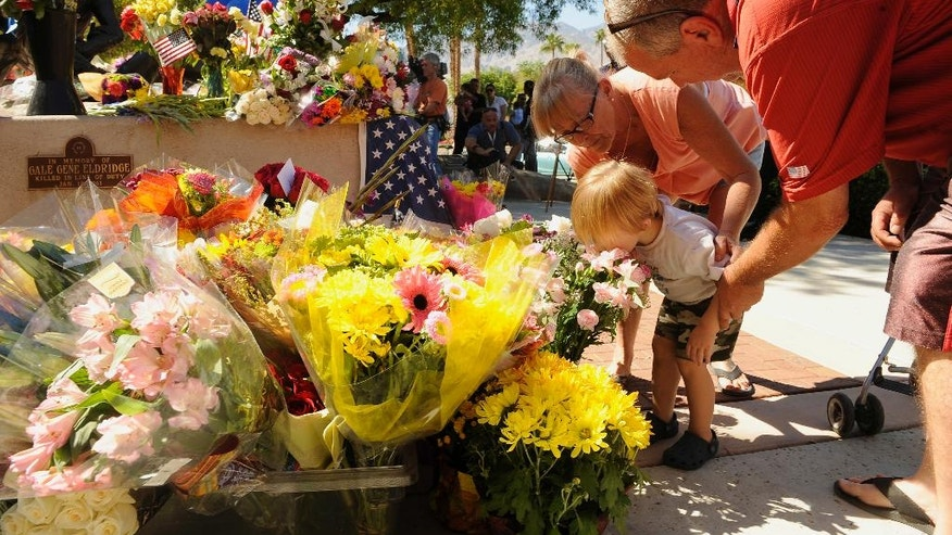 "Two-year-old Jayden Bunnell kisses flowers at the urging of his grandparents Barbara Bunnell and J.D. Bunnell, from Cathedral City, Calif., for slain Palm Springs Police Officers Jose ""Gil"" Gilbert Vega and Lesley Zerebny, in front of the police station in Palm Springs, Calif., Sunday, Oct. 9, 2016. Vega and Zerebny, trying to resolve a family dispute, were killed Saturday when a man they had been speaking with suddenly pulled out a gun and opened fire on them, the city's police chief said. (AP Photo/Rodrigo Pena)"