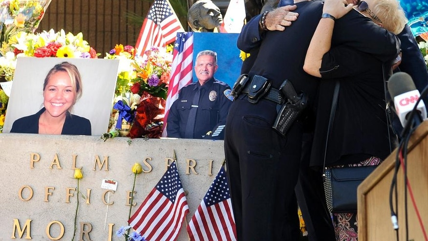 "Palm Springs councilmembers Ginny Foat, far right and J.R. Roberts, hug Palm Springs Police Chief Bryan Reyes at the conclusion of a press conference for slain Palm Springs Police Officers Jose ""Gil"" Gilbert Vega and Lesley Zerebny, in front of the police station in Palm Springs, Calif., Sunday, Oct. 9, 2016. Vega and Zerebny, trying to resolve a family dispute, were killed Saturday when a man they had been speaking with suddenly pulled out a gun and opened fire on them, the city's police chief said. (AP Photo/Rodrigo Pena)"
