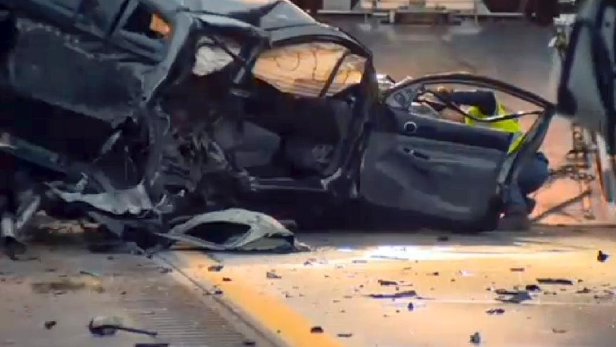 In this still image from video provided by WCAX-TV, a worker attaches a wrecker cable to a vehicle on Interstate 89 early Sunday, Oct. 9, 2016, in Williston,Vt., after a wrong-way driver caused a crash just before midnight that killed multiple people, before stealing a police cruiser, striking several vehicles and injuring several people.  (WCAX-TV via AP)