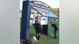 Wendy Peterson, left, and Kristi McKnight, right, staff at Harwood Union High School, update a marquee in front of the school Monday, Oct. 10, 2016, in Duxbury, Vt., with an invitation to the public to attend a vigil for four students from the school, and a fifth member of the community, killed in a wrong-way crash on Interstate 89 Sunday. The five teenagers were killed when a pickup truck speeding in the wrong direction on the highway slammed into their car, sending it up in flames. (AP Photo/Wilson Ring)