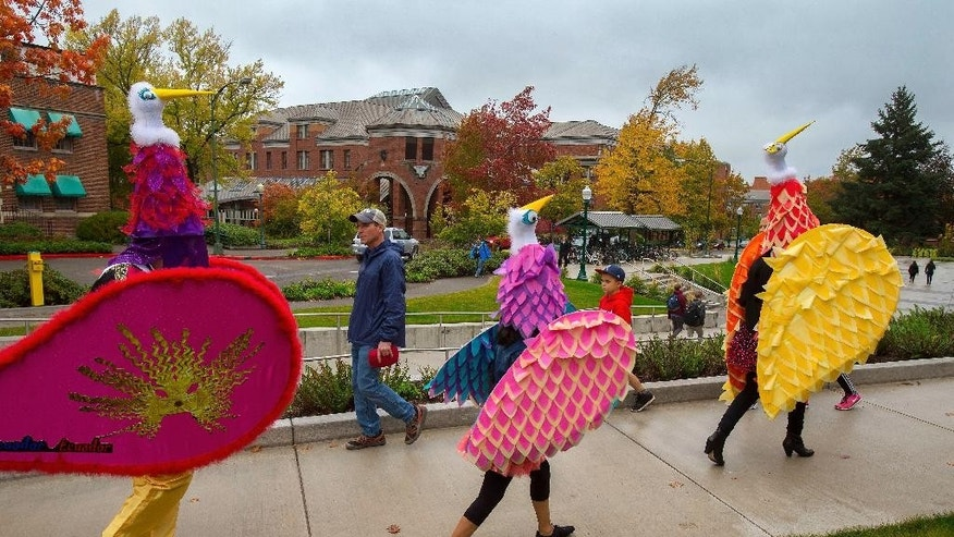 Ecuadorian dancers return from a performance on the University of Oregon campus during a daylong celebration of Indigenous Peoples' Day in Eugene, Ore. Monday, Oct. 10, 2016. Observed by a growing number of cities in place of Columbus Day, it follows a Eugene City Council resolution last March establishing the second Monday in October as Indigenous Peoples' Day. The campus event, sponsored by the Native American Student Union, is expected to be an annual celebration of indigenous spirit and culture. (Brian Davies/The Register-Guard via AP)
