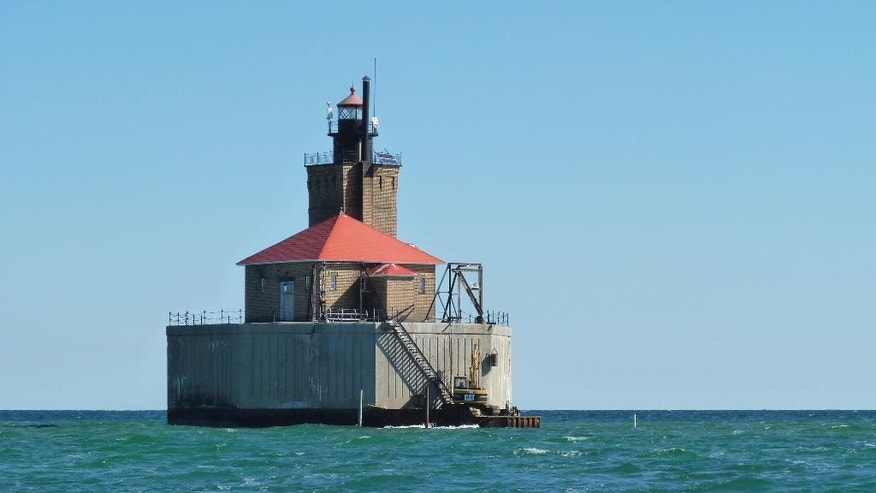 In this photo taken Monday, Sept. 12, 2016, the Port Austin Reef Lighthouse is seen from a boat more than two miles from the Michigan shore in Lake Huron's Saginaw Bay near Port Austin, Mich. Members of the nonprofit Port Austin Reef Light Association have worked for decades to restore the structure, which was last inhabited by light keepers in 1952. (AP Photo/Roger Schneider)
