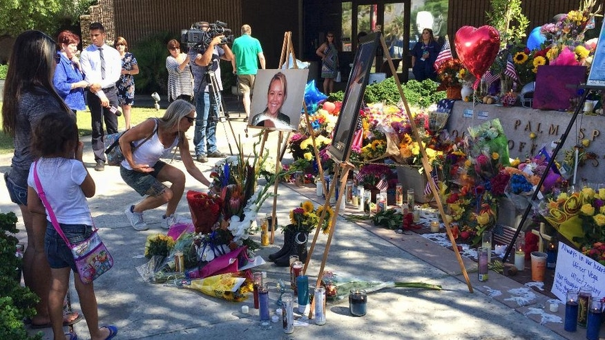 """People leave flowers at a memorial for Palm Springs Police Officers Lesley Zerebny, and Jose """"Gil"""" Gilbert Vega,seen in photos placed in front of the police station in Palm Springs, Calif., on Monday, Oct. 10, 2016. Both Southern California officers were fatally shot over the weekend. (AP Photo/Amy Taxin)"""