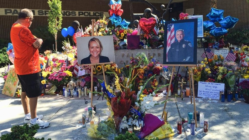 """A visitor pays his respect at a memorial for Palm Springs Police Officers Lesley Zerebny, and Jose """"Gil"""" Gilbert Vega,seen in photos placed in front of the police station in Palm Springs, Calif., on Monday, Oct. 10, 2016. Both Southern California officers were fatally shot over the weekend. (AP Photo/Amy Taxin)"""
