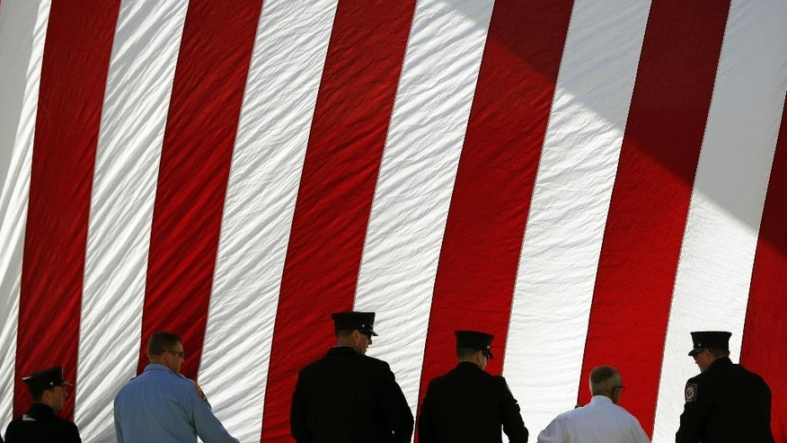 Firefighters roll up a flag after a ceremony at the New York State Fallen Firefighters Memorial at the Empire State Plaza on Tuesday, Oct. 11, 2016, in Albany, N.Y. The names of eight firefighters who died in the line of duty were added to the memorial Tuesday. (AP Photo/Mike Groll)