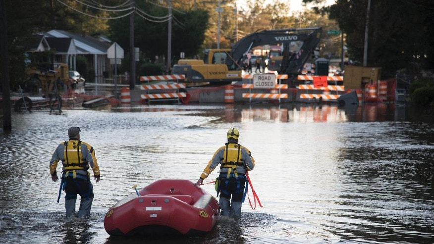 A swift water rescue team down a street covered by floodwaters caused by rain from Hurricane Matthew in Lumberton, N.C., Monday, Oct. 10, 2016. (AP Photo/Mike Spencer)