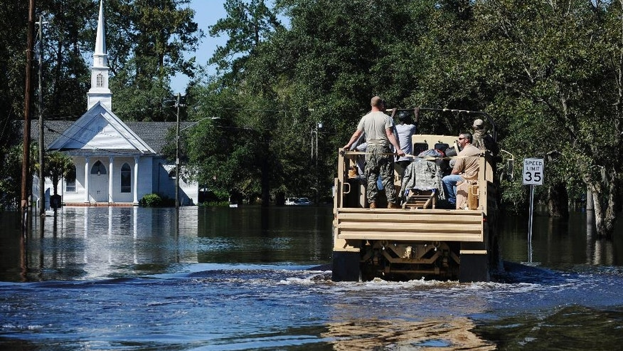 A National Guard high-water vehicle drives through Nichols, S.C. on Tuesday, Oct. 11, 2016. About 150 people were rescued by boats from flooding in the riverside village of Nichols on Monday. (AP Photo/Rainier Ehrhardt)