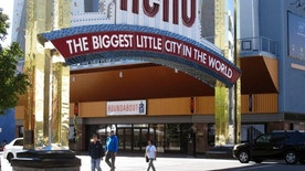 Pedestrians walk beneath the famous Reno arch as traffic passes on Virginia Street in downtown Reno, Nev. on Tuesday, Oct. 11, 2016. Detectives are reviewing witness accounts and some ``horrifying'' cellphone video while they consider filing a criminal complaint after a pickup truck plowed into a crowd of people during a Native American rights demonstration in downtown Reno, the police chief said Tuesday.  (AP Photo/Scott Sonner).