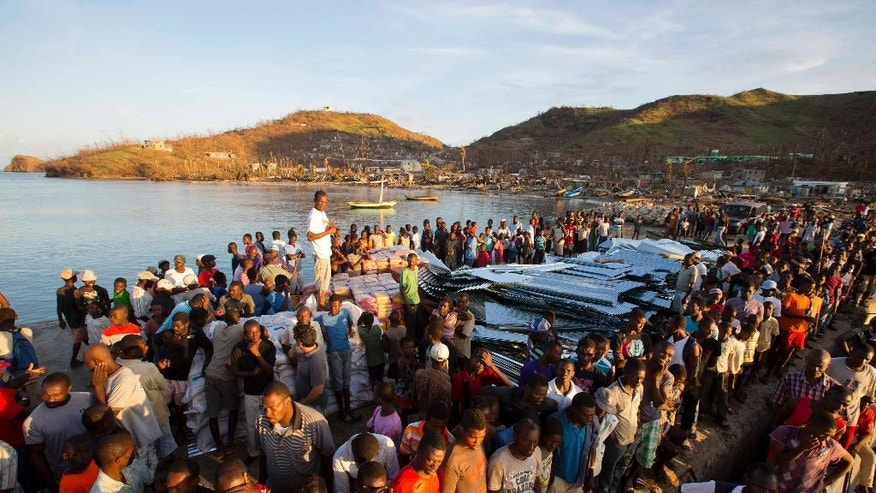 Residents line up for food after Hurricane Matthew in Anse D'Hainault, Haiti, Tuesday, Oct. 11, 2016. Nearly a week after the storm smashed into southwestern Haiti, some communities along the southern coast have yet to receive any assistance, leaving residents who have lost their homes and virtually all of their belongings struggling to find shelter and potable water. (AP Photo/Dieu Nalio Chery)