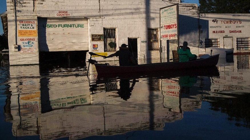 Ryan Christian and Delores Miller canoe down West 5th Street after checking on Miller's elderly mother's home in downtown Lumberton after Hurricane Matthew caused downed trees, power outages and massive flooding along the Lumber River, Tuesday, Oct. 11, 2016 in Lumberton, NC. (Travis Long/The News & Observer via AP)