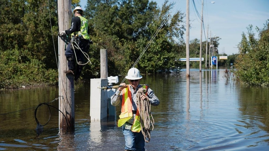 A lineman works to restore power lines near I-95 after the area was flooded by rain from Hurricane Matthew in Lumberton, N.C., Tuesday, Oct. 11, 2016. (AP Photo/Mike Spencer)