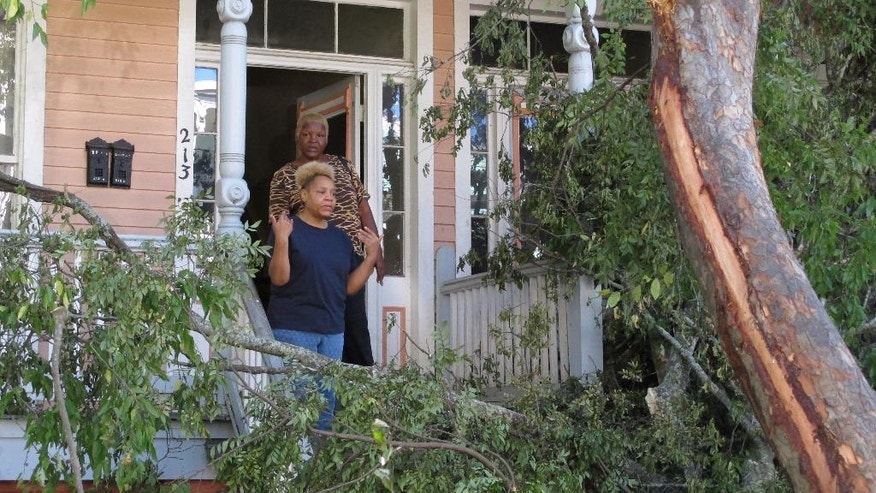 Sharon Kelsey, front, and her cousin, Pamela Williams, stand on the front port of the Victorian home in Savannah, Ga., where Kelsey lives in a first floor apartment Monday, Oct. 10, 2016. A large tree crashed across the front of the house as Hurricane Matthew raked the Georgia coast over the weekend. Matthew did extensive damage to the signature tree canopy in Savannah.  (AP Photo/Russ Bynum)