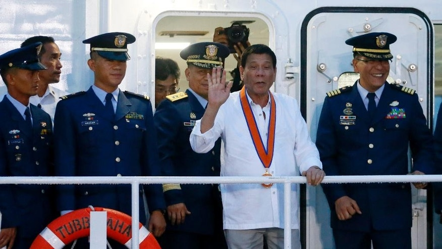 Philippine President Rodrigo Duterte waves from the deck as he tours the newly-commissioned Philippine Coast Guard vessel the BRP Tubbataha during its 115th anniversary celebration Wednesday Oct.12, 2016 in Manila, Philippines. Duterte said he has instructed his defense chief not to prepare for joint exercises with the U.S. military next year as he moved to realize his threat to scrap the high-profile symbol of his country's treaty alliance. Duterte, however, reiterated that he will not abrogate a 1951 Mutual Defense Treaty with Washington. (AP Photo/Bullit Marquez)
