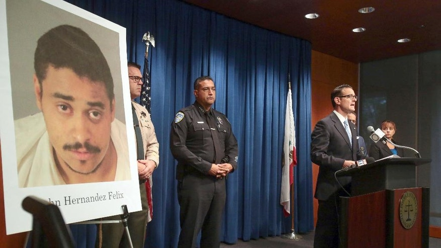 """Riverside County District Attorney Mike Hestrin, at podium, announces he is charging John Felix, seen in poster, with two counts of first-degree murder and other crimes for the killing of two Palm Springs police officers, at a news conference in Riverside, Calif., Wednesday, Oct. 12, 2016. Hestrin said Felix """"wanted to kill police officers"""" and prepared for the attack with armor and special ammunition in the confrontation Saturday, Oct. 8, that left two officers dead and one wounded. (Richard Lui/The Desert Sun via AP)"""