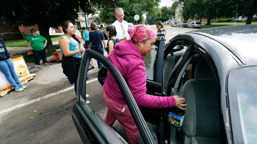 In this Thursday, Sept. 15, 2016 photo, Aurora Marte, of Storm Lake, Iowa, loads food into her car during a drive-by pantry sponsored by the Storm Lake school district, in Storm Lake, Iowa. Storm Lake has a low unemployment rate, vibrant downtown and tree-lined neighborhoods, but it's also facing a surge in hunger that's familiar to rural communities across the country. (AP Photo/Charlie Neibergall)