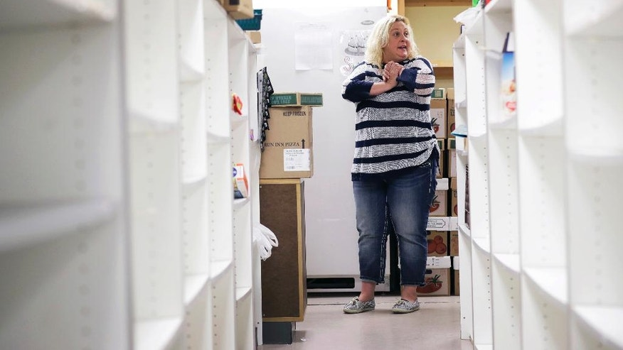 In this Thursday, Sept. 15, 2016 photo, Upper Des Moines Opportunity food pantry staff member Melissa Keller stands among empty shelves in the pantry in Storm Lake, Iowa. Storm Lake has a low unemployment rate, vibrant downtown and tree-lined neighborhoods, but it's also facing a surge in hunger that's familiar to rural communities across the country. (AP Photo/Charlie Neibergall)