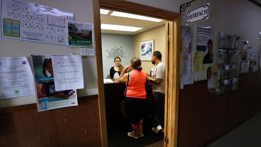 In this Thursday, Sept. 15, 2016 photo, Maria Medel, center, and Francisco Garcia, right, talk with a worker at the counter in the Upper Des Moines Opportunity food pantry, in Storm Lake, Iowa. Storm Lake has a low unemployment rate, vibrant downtown and tree-lined neighborhoods, but it's also facing a surge in hunger that's familiar to rural communities across the country. (AP Photo/Charlie Neibergall)